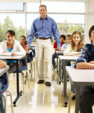 Teacher walking among seated students in the classroom.